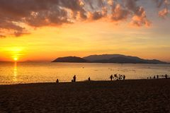 Seascape with Colorful Clouds, Orange Sky, Beach, People and The Sun at Sunrise in Nha Trang royalty free stock photography