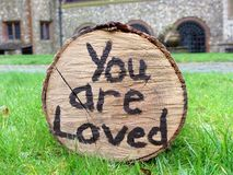 You are loved written on side of log on green grass stock photography