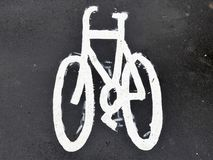 Painted bicycle sign on asphalt pavement royalty free stock images