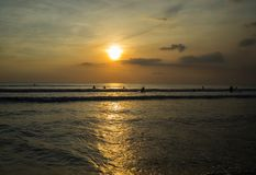 Sunset time and people activities in the beach, Kuta-Bali, Indonesia. A photo was taken in sunset time where many people swims in the beach Stock Image
