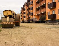Yellow old paver on the background of the road, prepared for the laying of asphalt and a new house. stock image