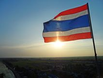 Photo of waving Thai flag of Thailand with the sun shines in the evening background. Royalty Free Stock Photography