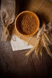 Photo of wheat bundle and sprouts on dark background. Wheat harvest, photo with copy space Royalty Free Stock Photo