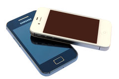 Photo of a white Apple Iphone device above a black Android Samsung Galaxy device, isolated in white background. BARCELONA, SPAIN - APR 08, 2014: Photo of a white Royalty Free Stock Images