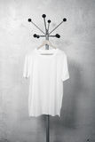 Photo of white blank tshirt hanging on the hanger. Vertical Stock Photography