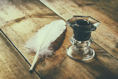 Photo of white Feather and inkwell on old wooden table Royalty Free Stock Image