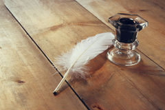 Photo of white Feather and inkwell on old wooden table Stock Photos