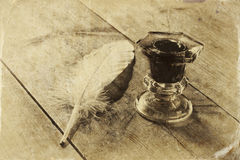 Photo of white Feather and inkwell on old wooden table Royalty Free Stock Photos