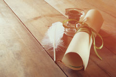 Photo of white Feather and inkwell on old wooden table Royalty Free Stock Images
