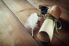 Photo of white Feather and inkwell on old wooden table Stock Image