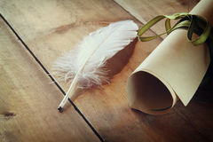 Photo of white Feather and inkwell on old wooden table Stock Photo