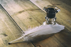 Photo of white Feather and inkwell on old wooden table. retro filtered image Royalty Free Stock Image