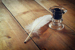 Photo of white Feather and inkwell on old wooden table. retro filtered image Stock Image