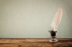 Photo of white Feather and inkwell on old wooden table. retro filtered image Stock Photo