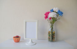 Photo White Frame on a wooden and Flowers in jar , cactus on wall background . Royalty Free Stock Photo