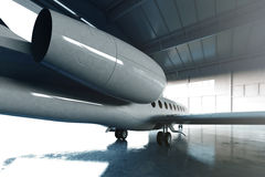 Photo of White Glossy Luxury Generic Design Private Jet parking in hangar airport. Concrete floor. Business Travel Stock Image