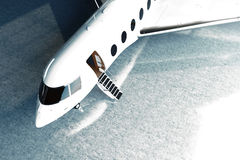 Photo of White Glossy Luxury Generic Design Private Jet parking in hangar airport. Concrete floor. Business Travel. Picture. Horizontal, top angle view pilot Royalty Free Stock Photos