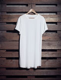 Photo of white long tshirt hanging on wood background. Vertical blank mockup Stock Image