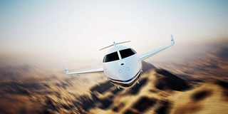 Photo of white modern and luxury generic design private jet flying in blue sky at sunrise.Uninhabited desert mountains Royalty Free Stock Photo