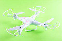 Photo of white quadrocopter on bright green background. Above view Stock Image
