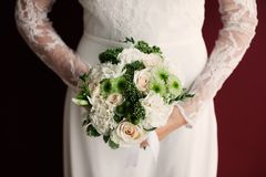 Elegant wedding bride bouquet with roses. Photo of white roses bouquet in hands of bride near red background royalty free stock image