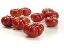 Marmande tomatoes on white table. Photo of a white table top with a bunch of Marmande tomatoes stock photos