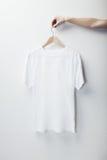 Photo of white tshirt hanging female hand Royalty Free Stock Photo