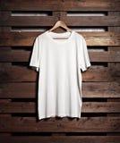 Photo of white tshirt hanging on wood background Stock Photo