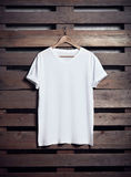 Photo of white tshirt hanging on wood background. Vertical blank mockup. Photo of blanc white tshirt hanging on wood background. Vertical Royalty Free Stock Photos