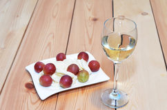 Photo of white wine glass and grapes with cheese on wooden table Stock Photography