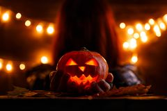 Photo of witch with long hair holding halloween pumpkin stock image