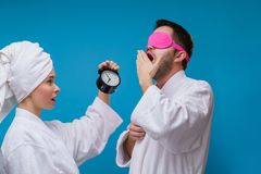 Photo of woman with alarm clock and man with pink blindfold. Photo of women with alarm clock and men with pink blindfold on empty blue background stock photo