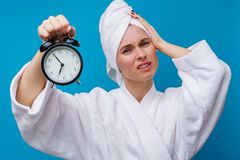 Photo of woman with alarm clock. On empty blue background royalty free stock images