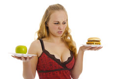 Photo of the woman with an apple and hamburger. Royalty Free Stock Photos