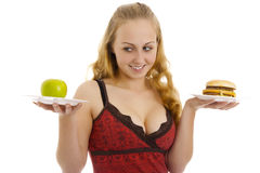 Photo of the woman with an apple and hamburger. Stock Images