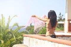 Photo of Woman in Black Bikini Holding Pink Scarf in Balcony