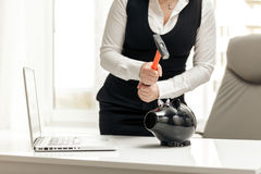 Photo of woman breaking piggy bank at office with hammer Royalty Free Stock Image