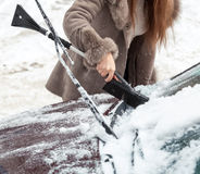 Photo of woman cleaning snow from car hood with brush stock photos