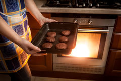Photo of woman cooking chocolate cookies in hot oven Stock Photo