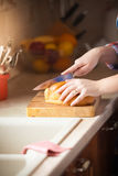 Photo of woman cutting bread on wooden desk Royalty Free Stock Images