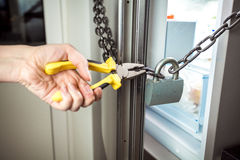 Photo of woman cutting chain on fridge with pliers Royalty Free Stock Images
