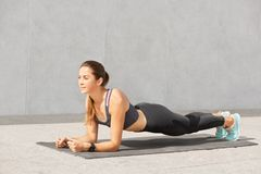 Photo of woman does plank static exercise, has cheerful expression, rejoices achieving good result, loosing weight, being in good. Shape, dressed in stock photos