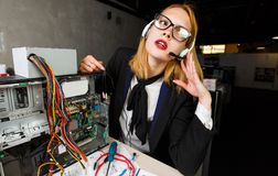 Photo of woman with glasses and headphones at table next to broken processor royalty free stock photography