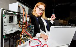 Photo of woman in glasses at table with broken processor and laptop. In office stock images