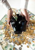 Photo of woman holding black pig moneybox on pile of coins Stock Photo