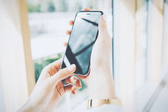 Photo woman holding modern smartphone in hands. Open space loft office. Reflection screen. Panoramic windows background Stock Images