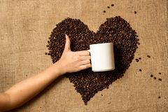 Photo of woman holding mug against heart made of coffee beans Stock Photography