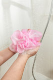 Photo of woman lathering pink sponge at shower Stock Photo