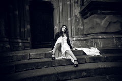 Photo of woman in long dress sitting on stone stairs at castle Stock Image