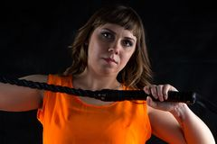 Photo of woman in orange dress with whip Stock Photography